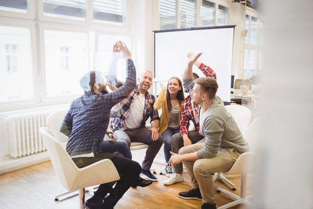 Excited-creative-business-people-giving-high-five-in-meeting-room-at-creative-office-1