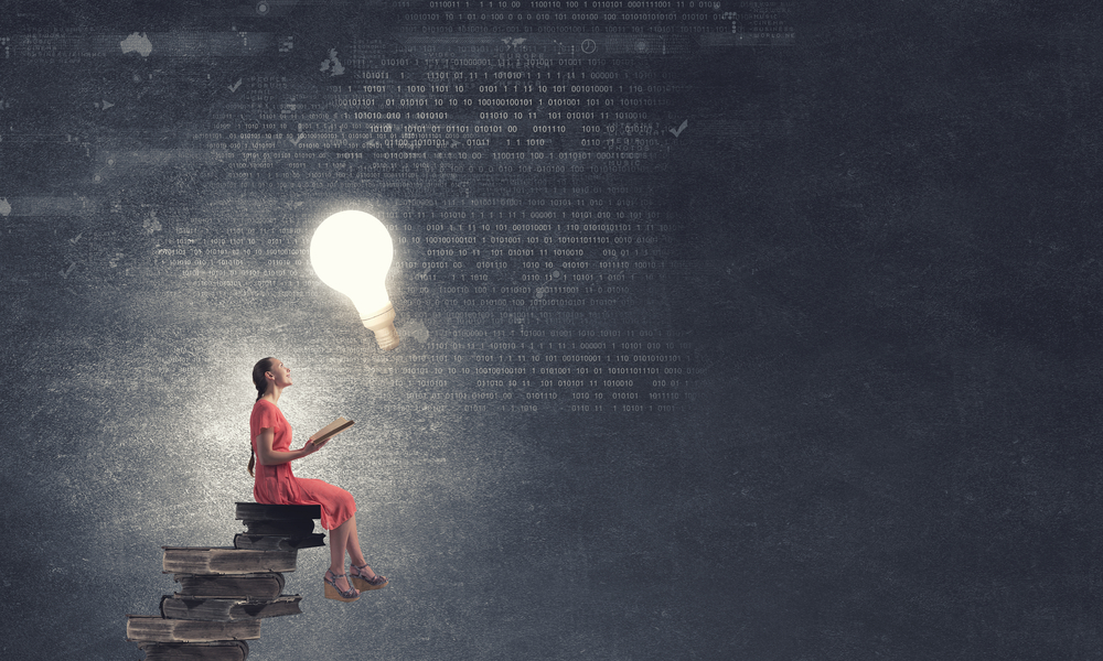Young girl sitting on stack of books and reading